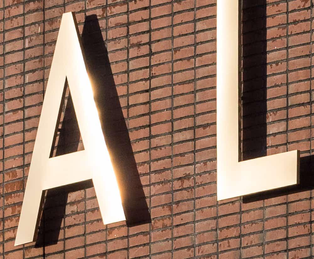 De reflectie van de zon op een letter van de Stopera in Amsterdam laat aan de rechterkant wat overstraling zien.